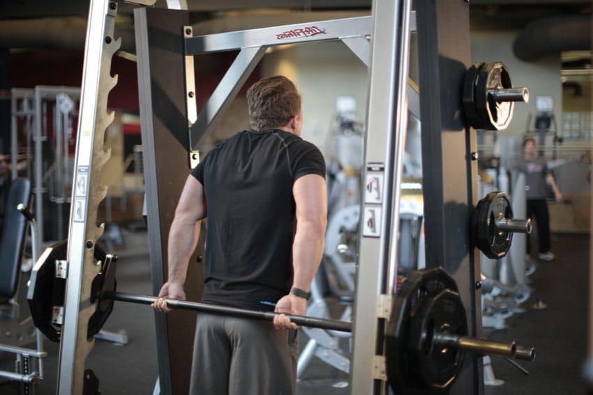 Encogimiento de hombros con barra por la espalda